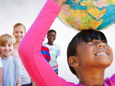 smiling children behind girl looking up holding a globe